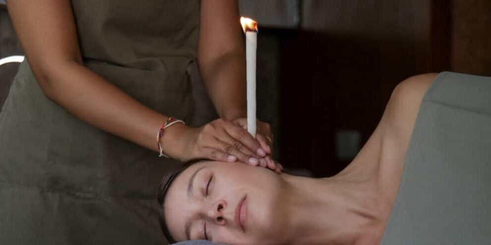 Woman receiving ear candle treatment at spa. Ear coning or therm
